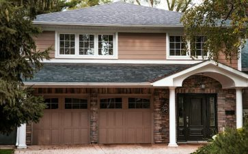 Large home with brick front, two garages and pillars in front of the front door