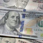 Hundred dollar bill laying on top of 50 dollar bills