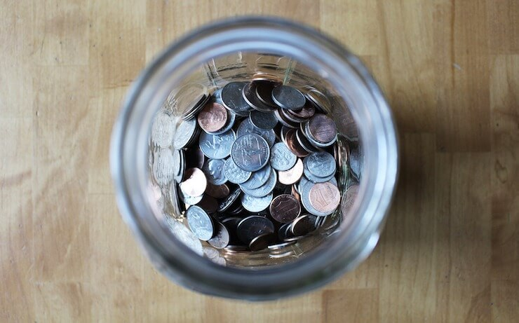 Large glass jar full of coins sitting on a wood table