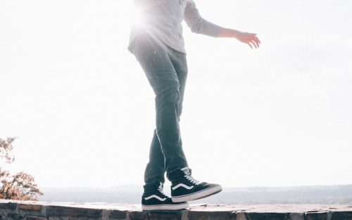 Man balancing on a wall wearing black sneakers and jeans