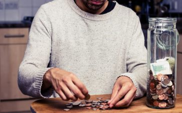 Man counting out coins on a table from a jar