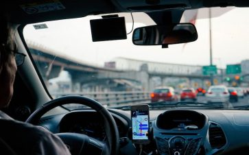 Man driving for a ride share company his phone displaying the route