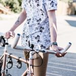 Man wearing palm tree shirt holding a bicycle outside