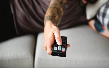 Man laying down on a grey couch changing the tv channel with a remote