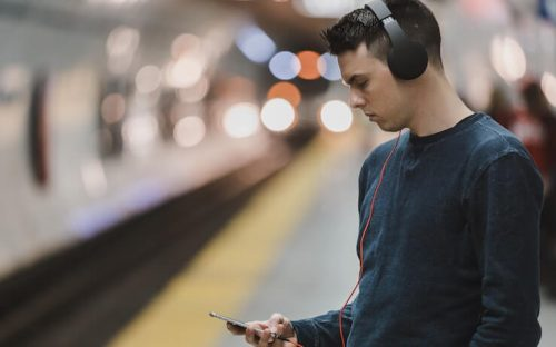 man looking at phone and listening to podcast while waiting for metro train to arrive