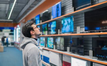 Man overwhelmed looking at a wall of TVs for sale
