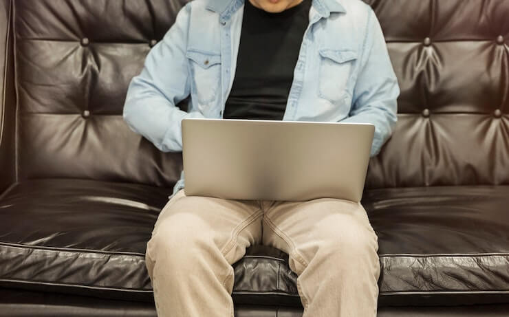 Man wearing a light jean jacket, black shirt and kakis sitting on black leather couch using his laptop
