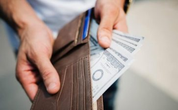 Man taking hundreds of dollars out of his leather wallet