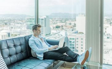 Man sitting on a couch using his laptop with an amazing view from the windows behind him