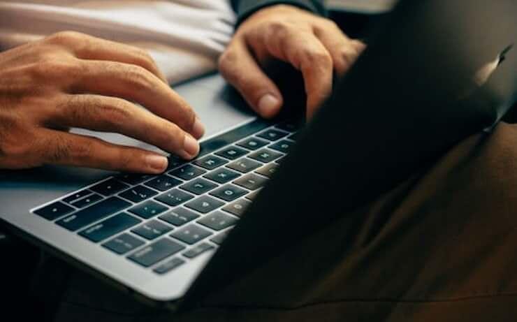 Hombre usando laptop apple respondiendo preguntas en línea para ganar dinero