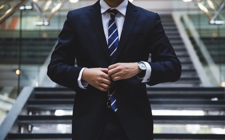Man adjusting his suit as he walks down stairs