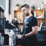 Young man working minimum wage job at coffee shop to make ends meet
