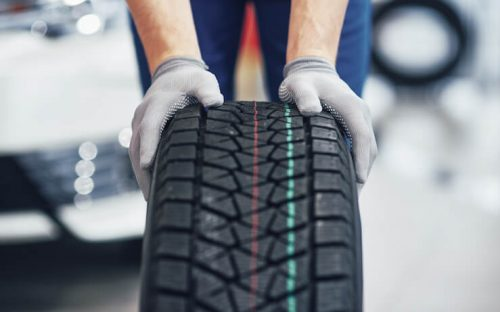 Mechanic wearing grey gloves rolling a new tire around the shot