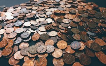 A bunch of pennies and coins spread across a table