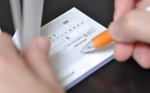 Person filling out a check in their checkbook using a pen with orange grip