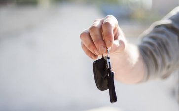 Person handing car keys to their new owner blurred background