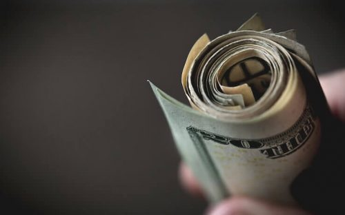Hand holding a rolled up bundle of cash bills