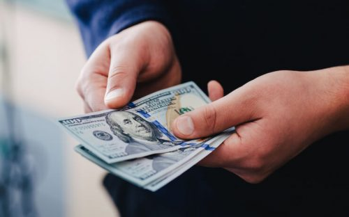 Person holding 100 dollar bills money they made through affiliate marketing