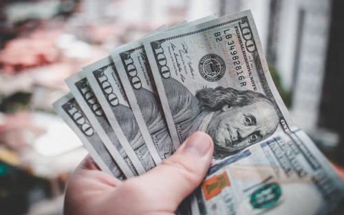 Person holding 100 dollar bills getting rich