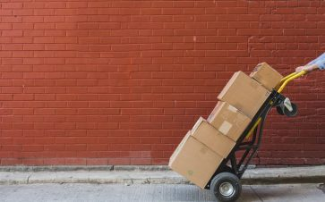 Person moving a bunch of boxes on a heavy duty dolly