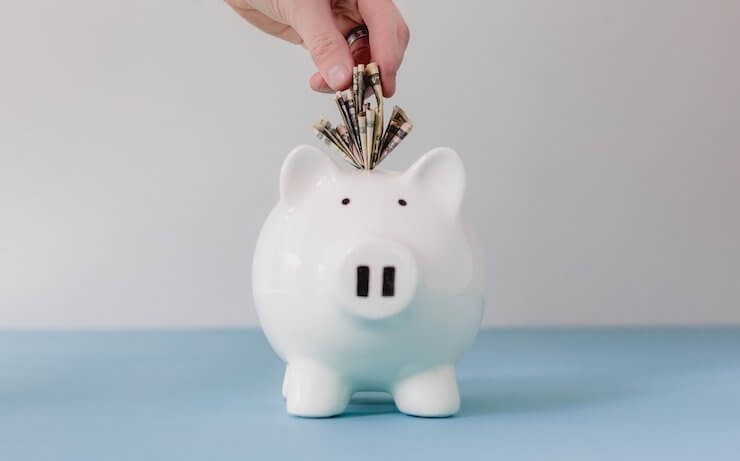 Person putting money into a piggy bank wearing a ring in white room with blue floor