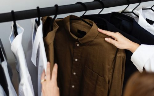 Person going through a rack of shirts with collars and black hangers