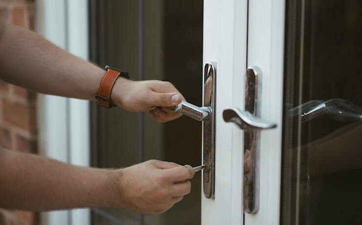 person wearing leather watch unlocking door with glass windows