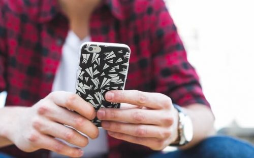 Person wearing a red plaid shirt holding a phone with black and white case with paper airplane shapes
