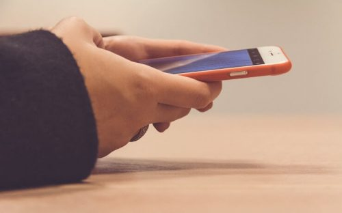 person using iphone with orange phone case