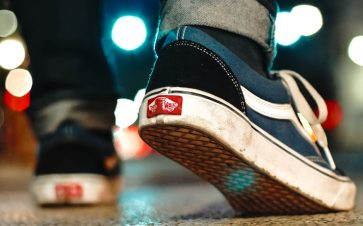 Person walking in dark blue vans sneakers on concrete