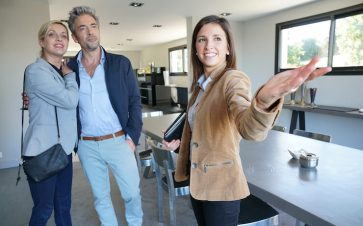 Real estate agent showing a couple a house
