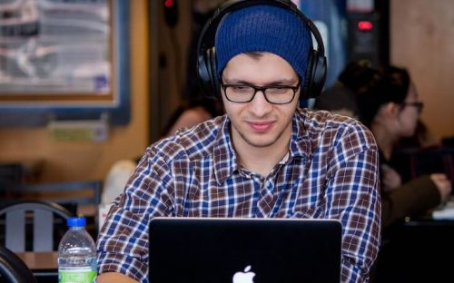 young man student wearing blue beanie using his computer wearing headphones in coffee shop
