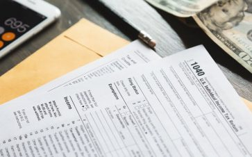 Tax forms next to a calculator or cash waiting to be filled out