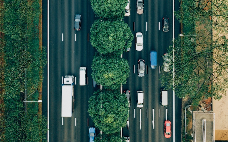 Birds eye view of cars with trees lining the road
