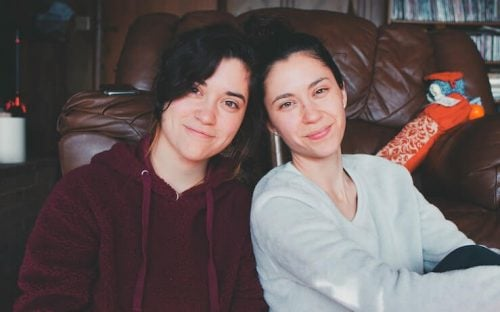Two girls hanging out at a house by a couch