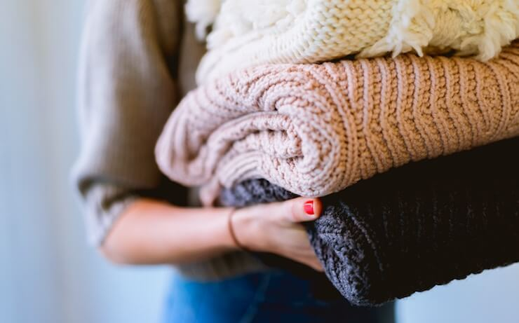 Woman folding and decluttering her blankets with pink manicure