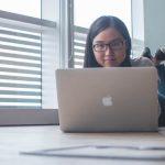 Woman designing shirts on her laptop