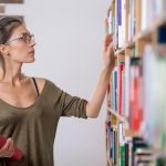 Woman going through all her old books to find ones to sell