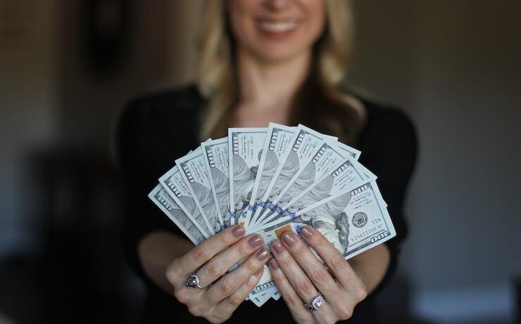 Wanita bisnis memegang kipas uang sambil tersenyum
