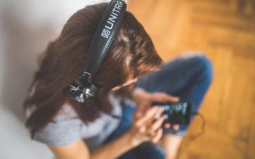 Woman listening to music on big headphones plugged into her phone