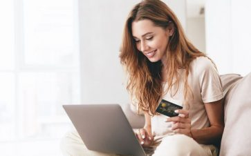 woman looking at computer with credit card in hand