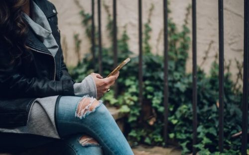 Woman looking at debt payoff apps on her phone sitting outside