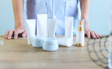 Woman standing behind bottles of product at her home to test out