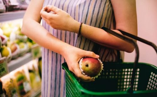 Woman putting asian pear into a green grocery basket