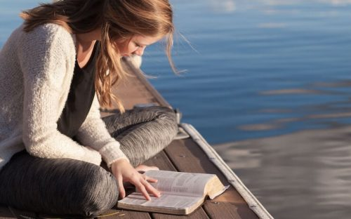 Woman wearing a sweater reading a big book by the lake
