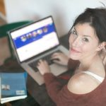 woman shopping online looking to the camera wearing red sweater
