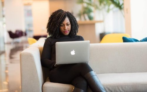 Woman sitting on couch with Apple laptop