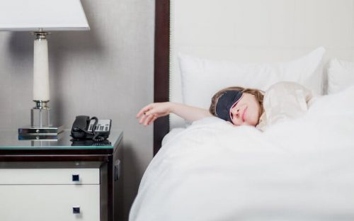 Woman Sleeping on Hotel Bed