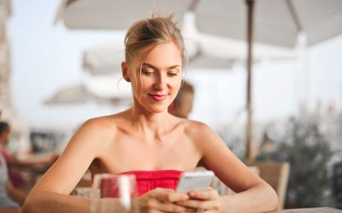 Woman smiling at her cell phone while using her free google play credits outside under umbrellas