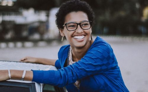 Woman smiling and leaning on her car that she was able to afford due to a personal loan